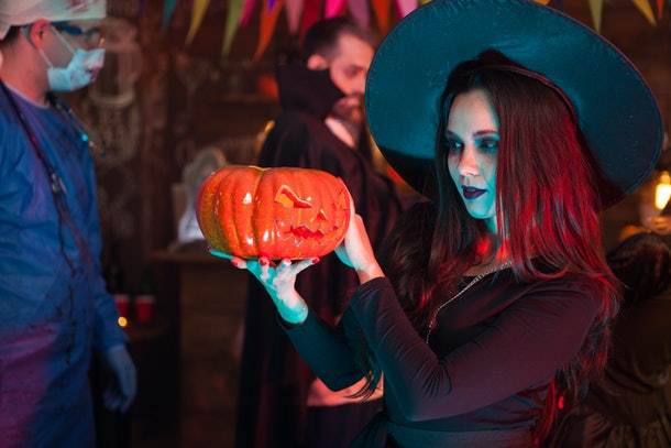 Portrait of beautiful woman dressed up like a witch doing dark magic on a pumpkin for halloween. Dracula at halloween party.