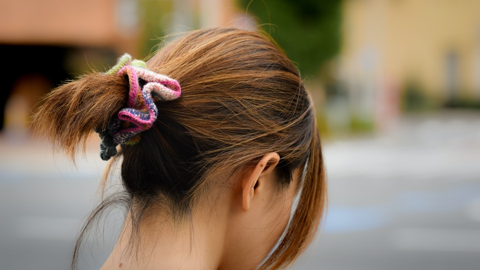 A brunette Japanses woman looks down and away, wearing a colourful scrunchie in her hair.