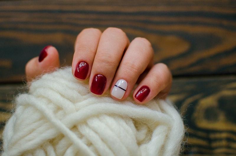 Luxury short manicure Burgundy on a black background. cozy autumn nails.