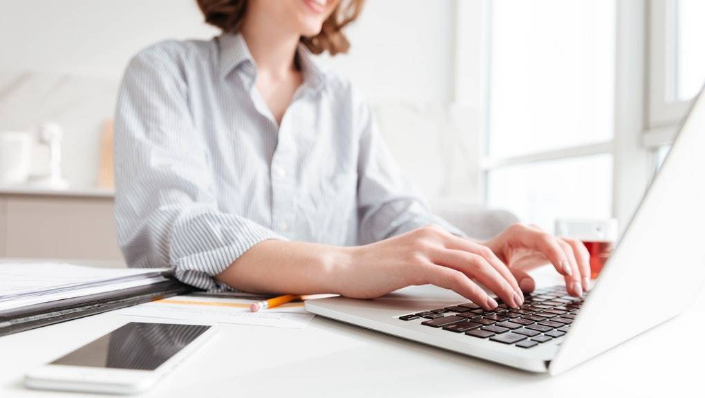 Cropped photo of pretty brunette woman typing email on laptop computer while sitting at home, selective focus on hand