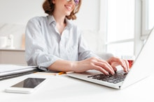 Cropped photo of pretty brunette woman typing email on laptop computer while sitting at home, select...