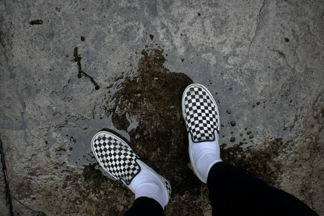 Checkered Vans in a puddle