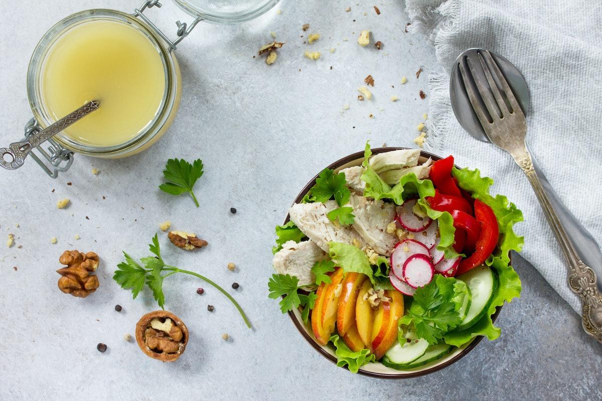 Summer lettuce with salad dressing vinaigrette. Salad with chicken, fresh vegetables, walnuts and gr...