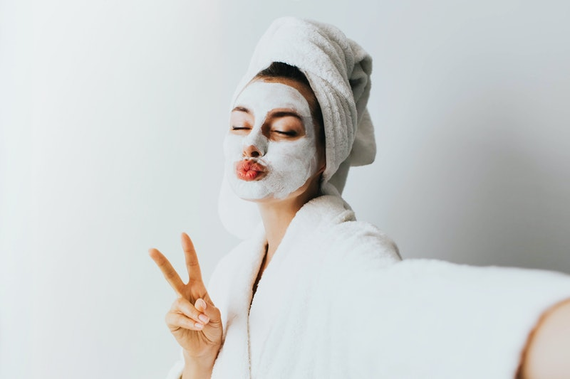 woman has fun with a facial mask.Self portrait of charming, stylish, pretty, model after bath wrapped in towel shooting selfie on front camera applying using face mask for her dry, oiled, sensual face