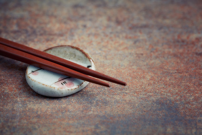 Wooden chopsticks and chopstick rest on rustic background. Close up. Copy space.