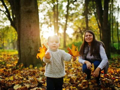 Mom with son on majestic autumn fall forest.