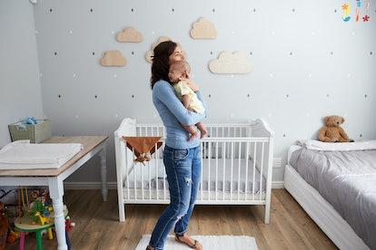 Mother Comforting Newborn Baby Son In Nursery