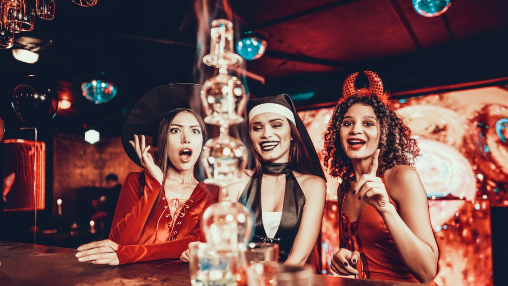 Women in Costumes Looking at Flaming Cocktail. Group of Smiling Young Friends Wearing Costumes Excited about Flaming Cocktails on Bar counter in Nightclub. Celebration of Halloween