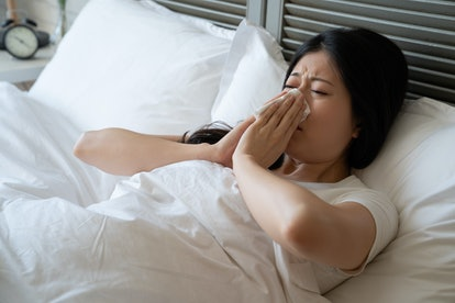 sick asian woman suffering from cold lying in bed with tissue sneezing. ill chinese female cover hide body under blanket blowing runny nose with handkerchief. Cold flu season rest at home concept.