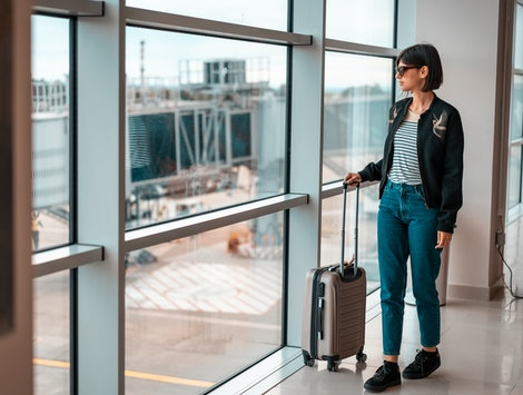Woman in bomber jacket and jeans waiting at the airport with carry-on luggage.