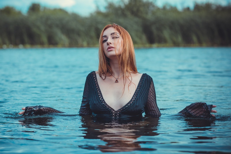 Sexy mystical woman in black bodysuit in water. Concept of femininity and sensual