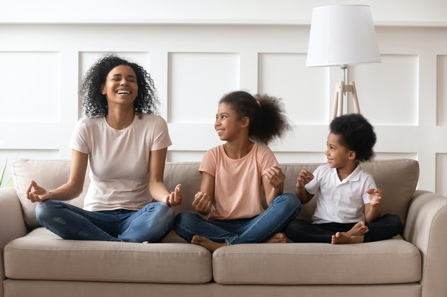 Happy laughing single black mom meditating with two kids at home, healthy african family mother teaching yoga little cute children having fun doing exercises relaxing sit in lotus position on sofa