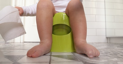 Funny baby boy sitting on chamberpot, Children's legs hanging down from a chamber-pot. Kid plays toi...