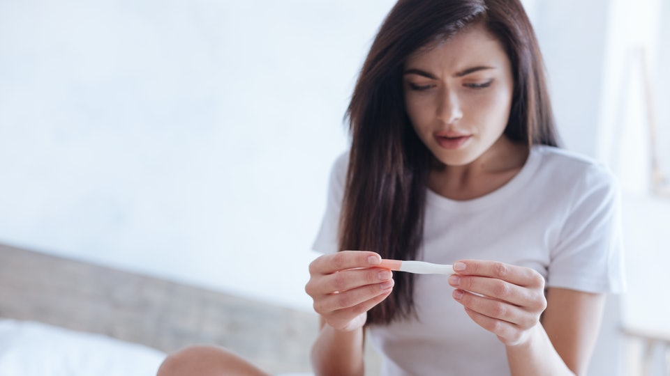 Young brunette cannot believe her eyes while checking pregnancy test