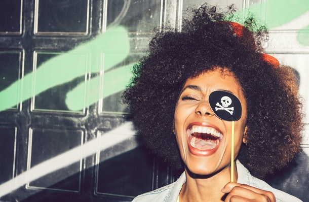 Beautiful young black woman having fun with a fake party pirate costume