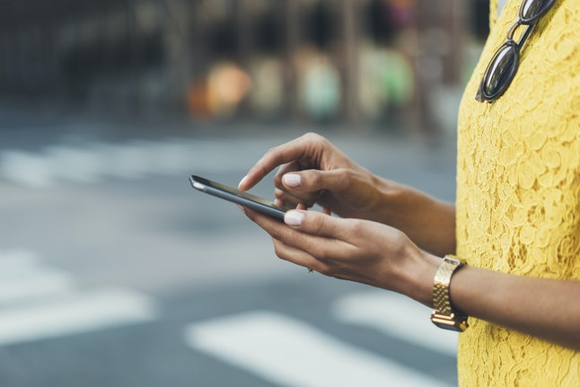 Close-up image of female hands using modern smart phone outside, woman'?s hands typing on touch screen of cellphone while standing at crosswalk in the city