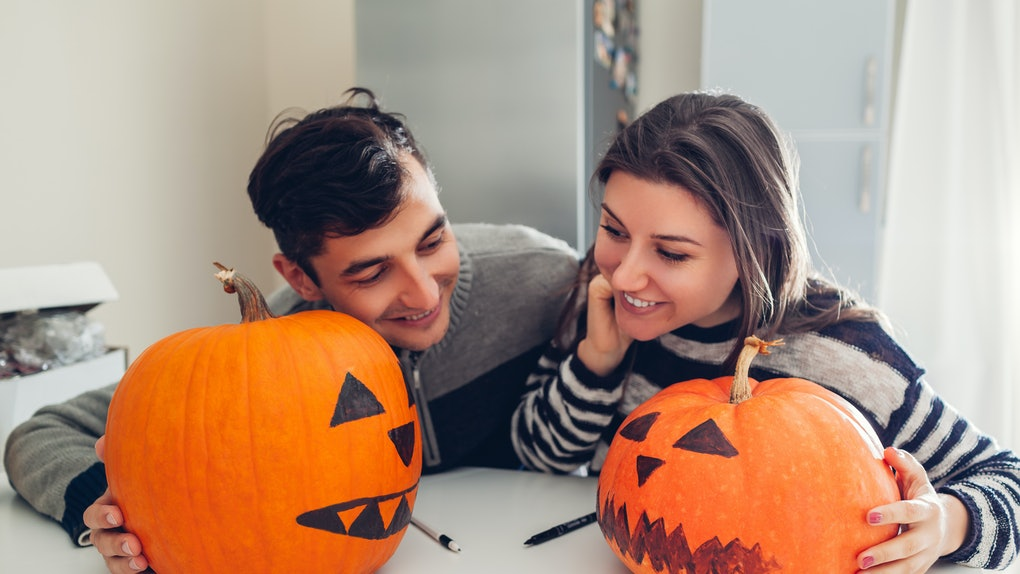 A couple making jack-o'-lanterns for Halloween may be in need of some pumpkin captions for couples for any selfies they snap with their masterpieces.