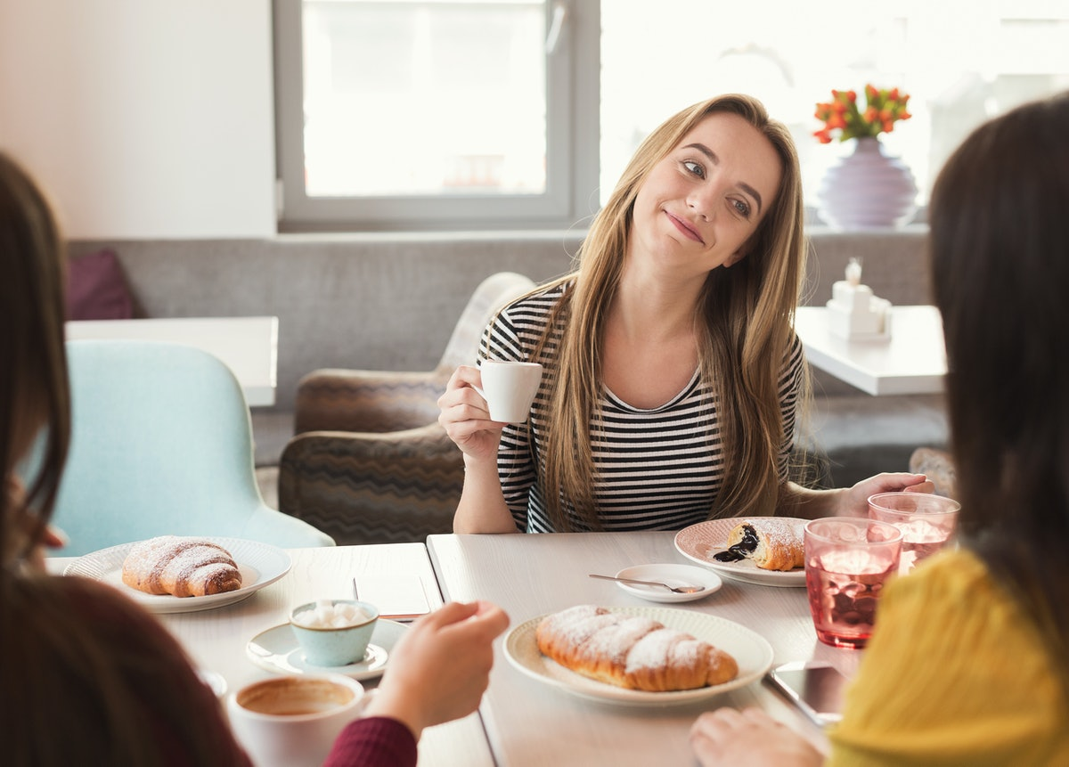 Happy girls at restaurant. Friends having brunch, chatting and gossipping at cafe