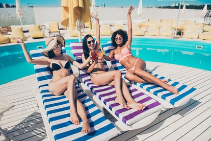 Nice attractive lovely glamorous cheerful cheery careless carefree slim thin fit sporty girls lying on sunbed at fashionable spa resort hotel club having fun clinking glasses congrats bachelor
