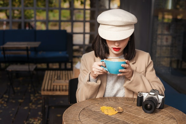 Mysterious woman in a hat is drinking coffee