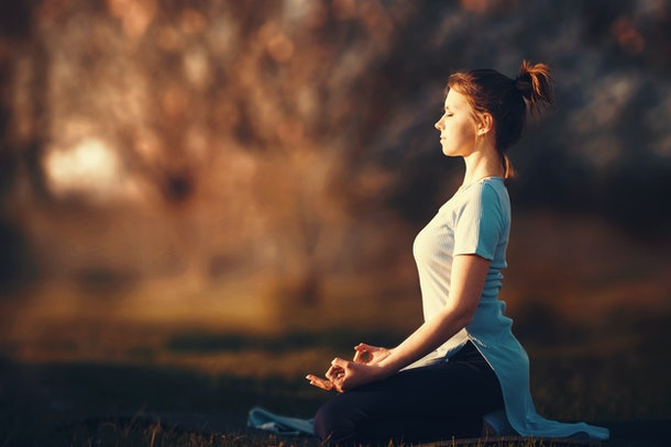 Woman meditating in the rays of the setting sun.