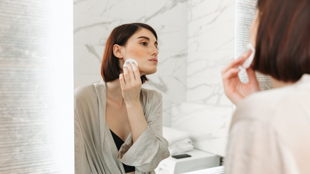 Beauty portrait of brunette woman with soft healthy skin removing makeup with cotton pad in hotel bathroom