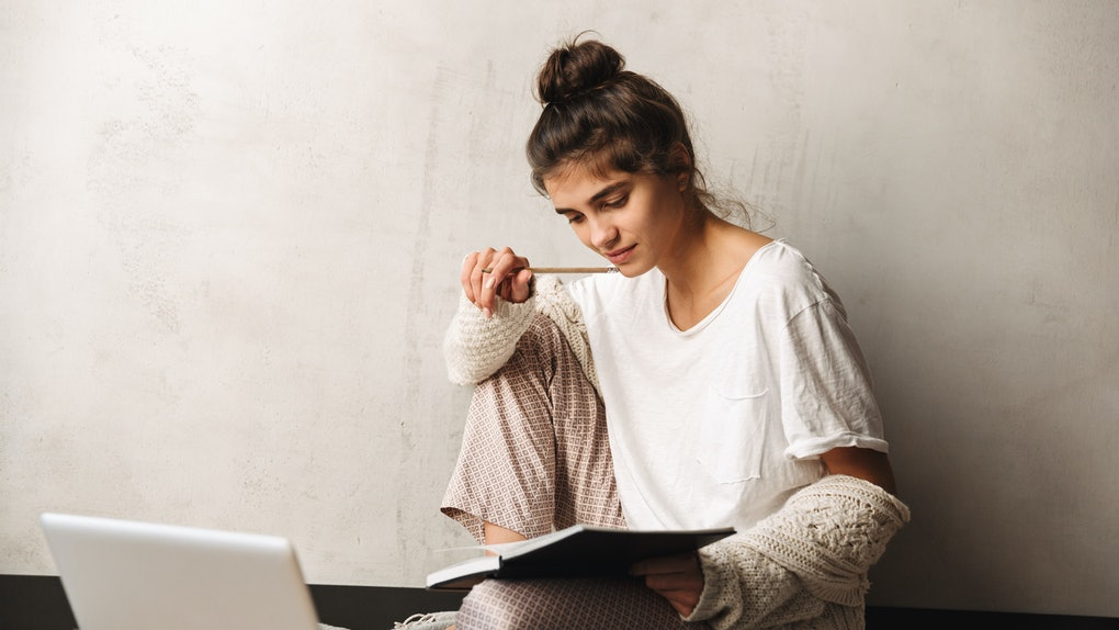 Photo of concentrated serious woman wearing leisure clothes writing in diary and using laptop while sitting on floor at home