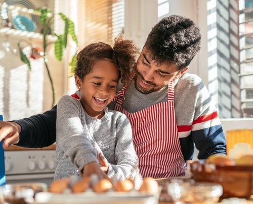 Photo of a smiling african american father and daughter baking in the kitchen and having fun.