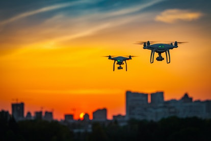 Two drone quad copters with high resolution digital camera flying aerial over spectacular sunset ora...