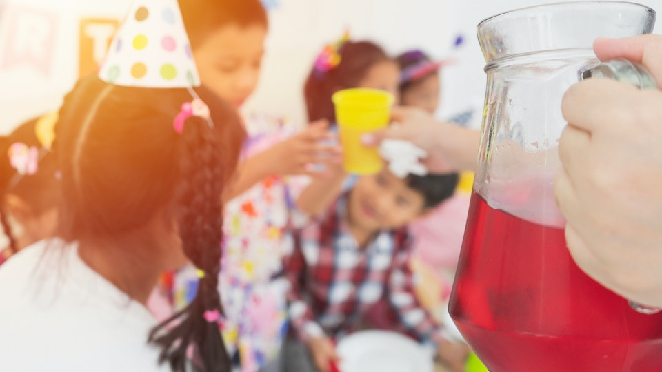 Close Up hands people holding Refreshing drink, Fruit juices or Iced beverages and cocktails in glass pitchers go to Happy group of cheerful children, friends celebrating having fun at birthday party