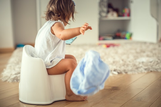 Infant child baby girl toddler sitting on potty training seat, using a smartphone. (age 1,5 years)