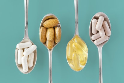 Healthy supplements on teaspoons against colorful background