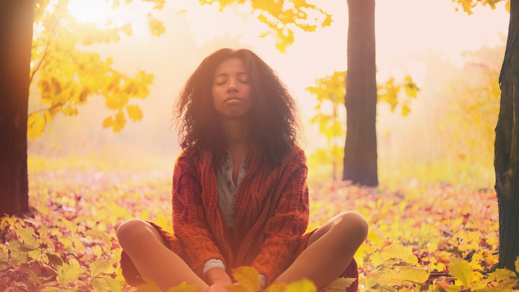 Young black woman relaxing in the autumn forest on a sunny day.