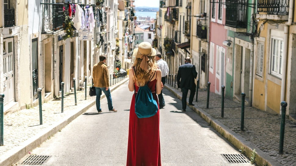 Young travel woman is walking on the beautiful old cozy street of Lisbon in Portugal