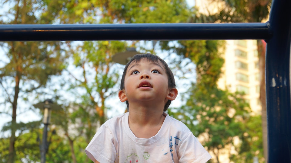 Cute and happy big eyes black hair Asian boy in dirty white T-shirt playing joyfully in the park playground