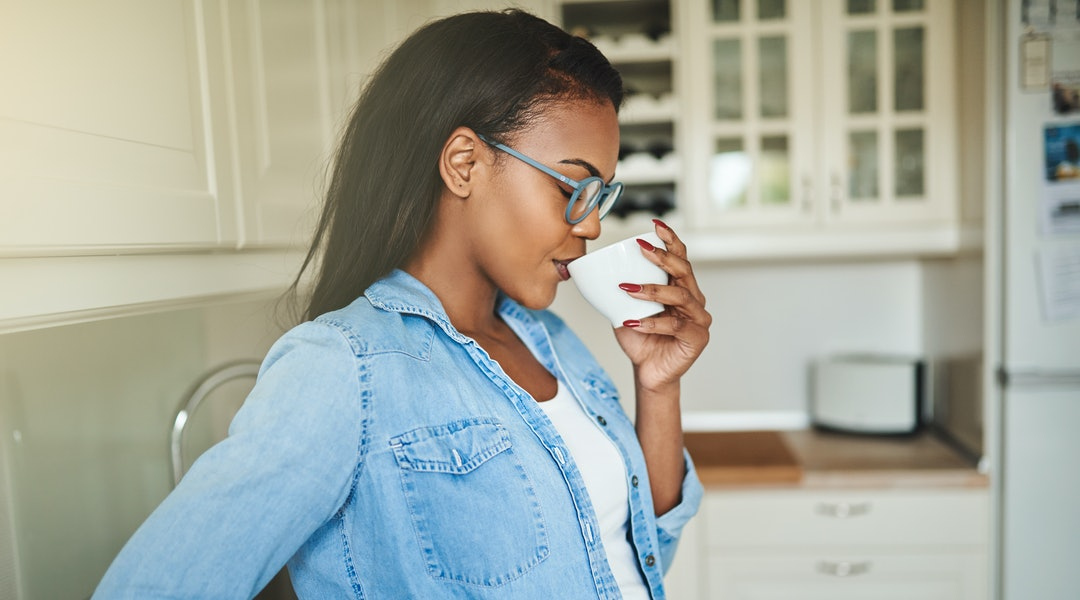 Content young African woman standing alone in her kitchen at home taking a sip from a cup of fresh coffee