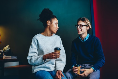 Multiracial couple talking to each other sitting with coffee cups, positive male and female friends discussing ideas and share opinions during break in office, cheerful man looking at colleague