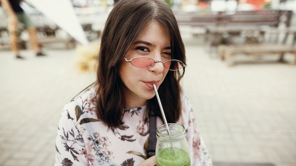 Stylish hipster boho girl drinking spinach smoothie in a glass jar with metal reusable straw at a street food festival.