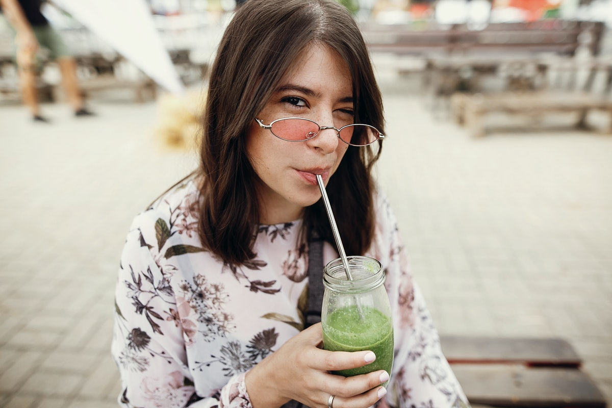 Stylish hipster boho girl drinking spinach smoothie in a glass jar with metal reusable straw at a st...