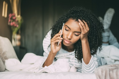 Beautiful serious thoughtful and sad black woman with curly hair using smartphone on bed