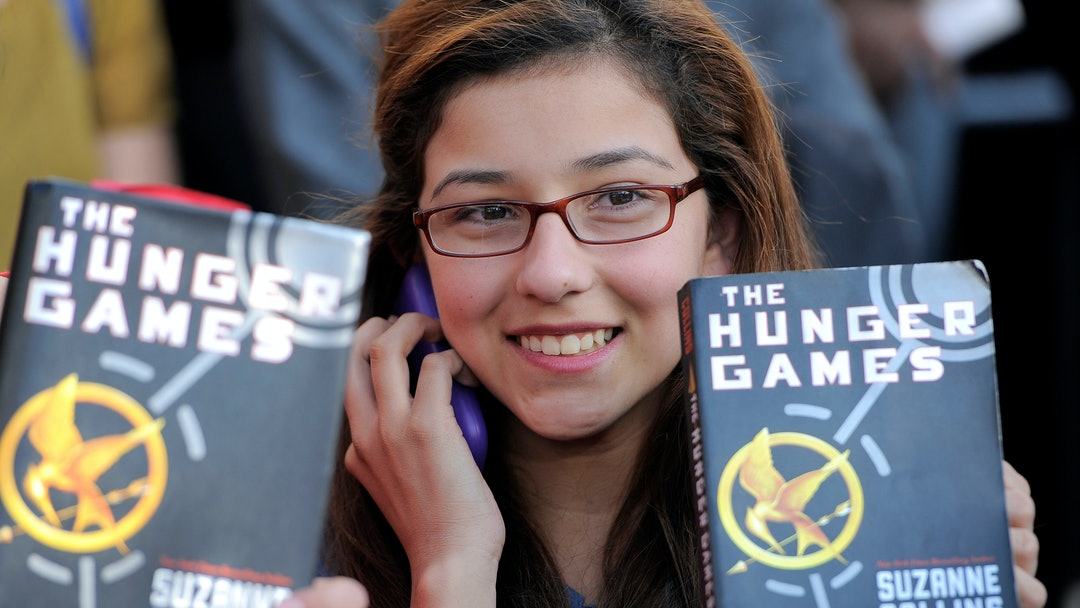 "A Hunger Game fan holds up a copy of the Hunger Games book at the world premiere of ""The Hunger Games"" on in Los Angeles"