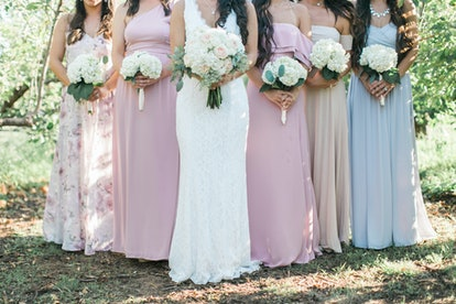 bride and bridesmaids holding wedding bouquets, pastel bridesmaids dresses, detail shot, copy space