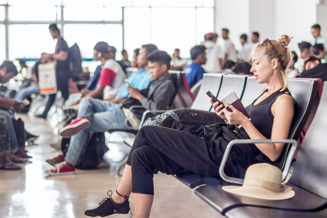 Casual sporty young blond female traveler using her cell phone while waiting to board a plane at the departure gates at the airport terminal. Boarding a plane by zone is meant to increase efficiency and minimize waiting.