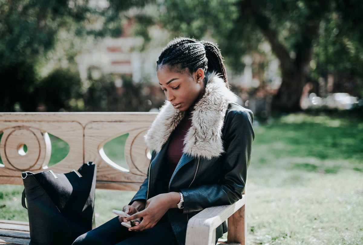 Woman sitting on a wooden park bench