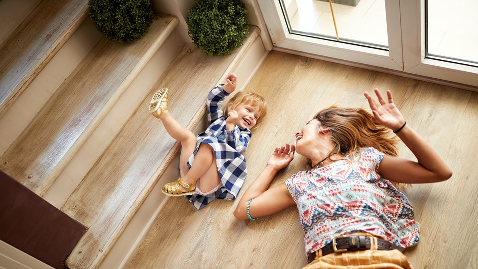 Babysitter with child having fun on the stairs