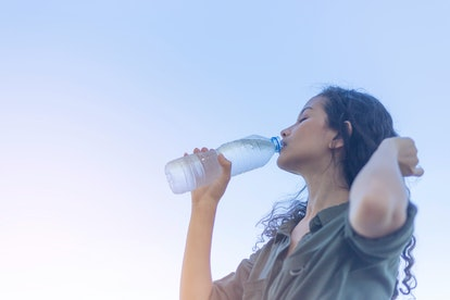 Happy beautiful young Asian woman drinking water with a plastic bottle in her hand. clean water are good for health and recovery concept