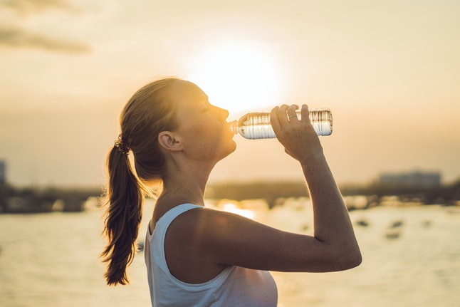 Sporty woman drinking water outdoor on sunny day.