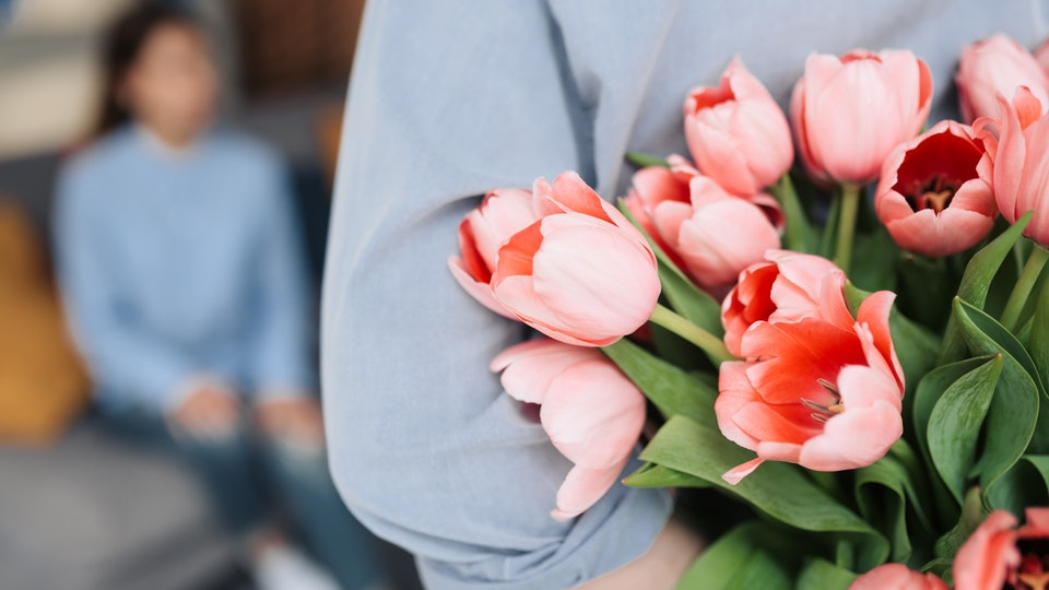 Unexpected moment in routine everyday life! Cropped photo of man's hands hiding holding chic bouquet of tulips behind back, happy woman is on background.