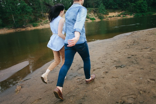 A couple in love runs along the shore. Two people running with their backs to the camera. The girl a...