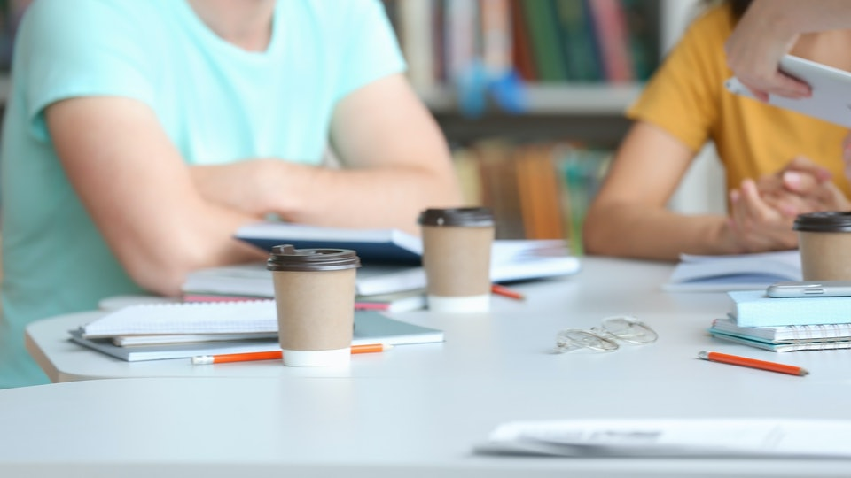 Young people studying at table in library, closeup